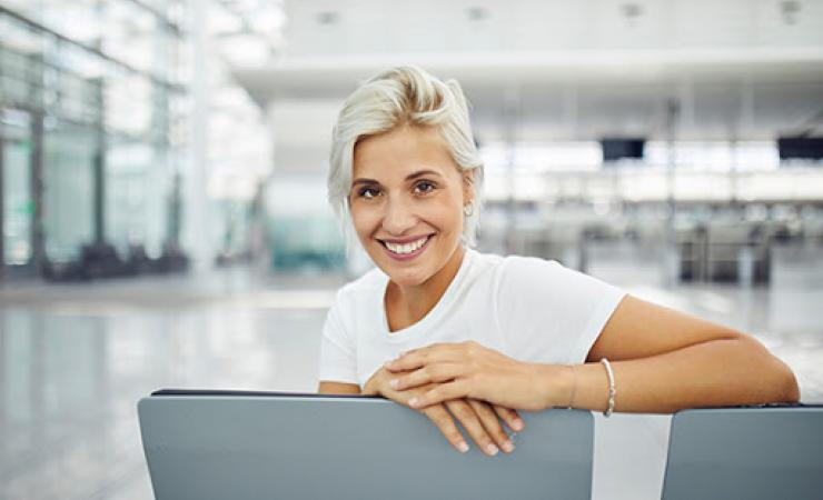 Woman sitting in airport smiling