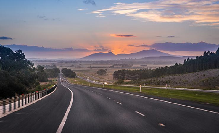 Highway with view of sunset over mountains