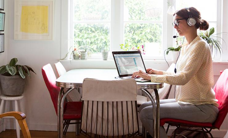 Woman with headphones working by window in Dining room
