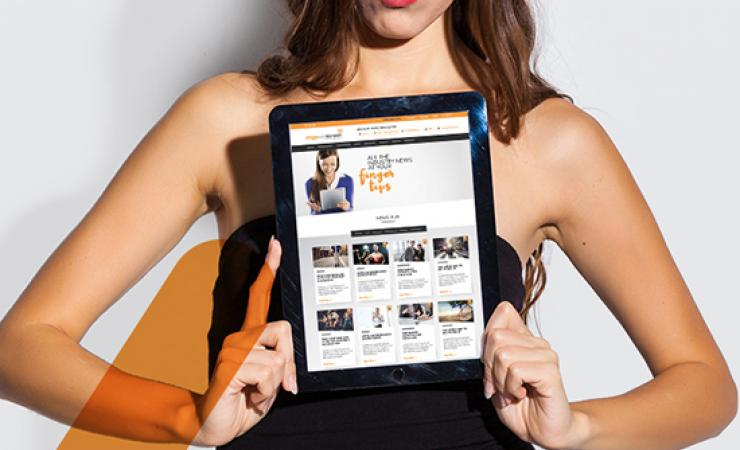 Image of woman holding up iPad with Stage's website news on the screen
