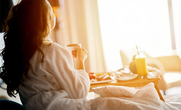 Lady relaxing in hotel room with breakfast