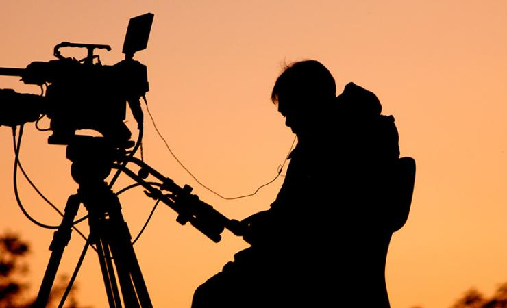 Silhouette of camera man at sunset