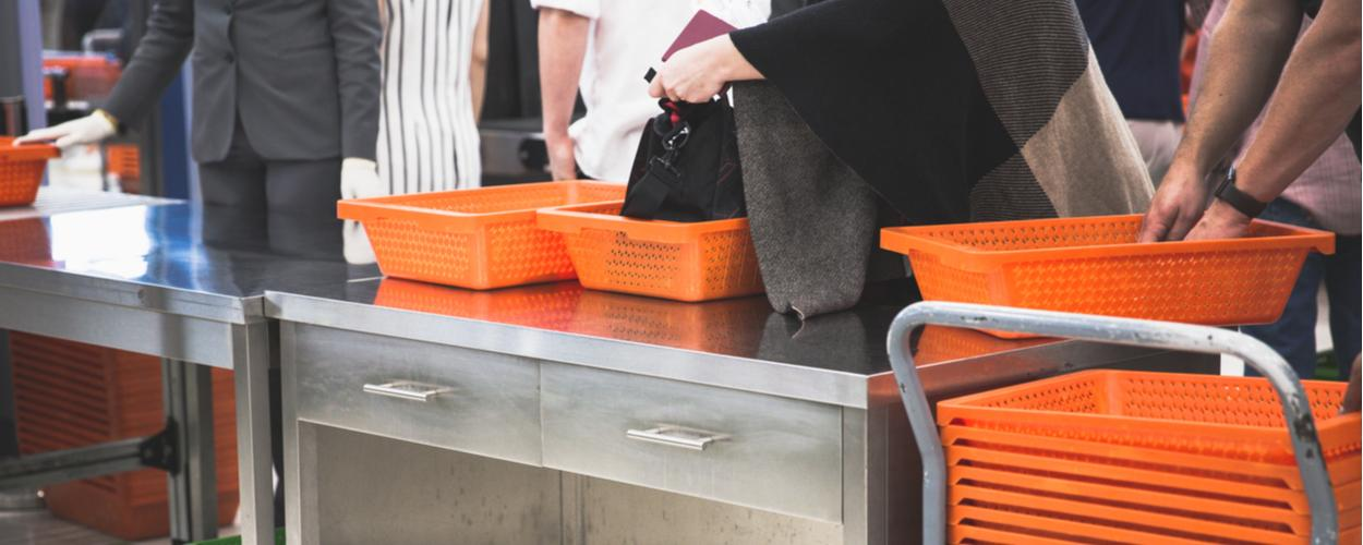People in line at the bag check with orange trays